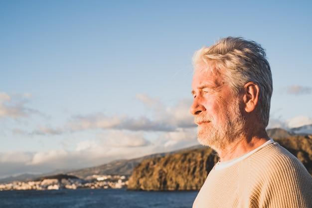 クローズアップとビーチで海を見ている悲しくて物思いにふける男の肖像画
