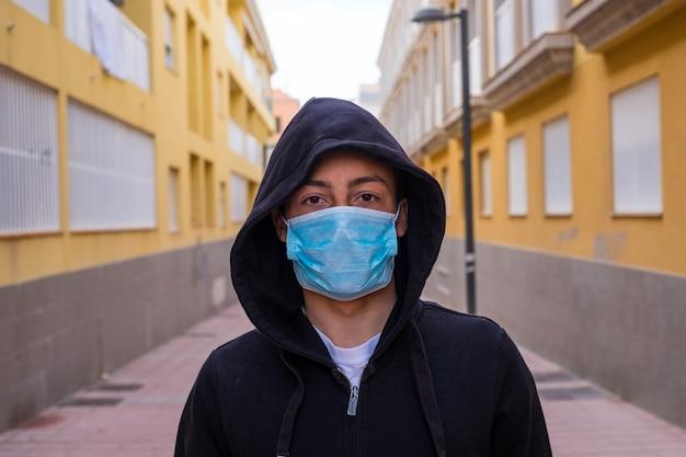 바이러스 또는 코로나바이러스(covid-19)와 같은 모든 유형의 질병을 예방하는 의료용 마스크를 쓴 십대의 클로즈업 및 초상화 - 마스크를 착용하려고 하는 카메라를 보고 있는 진지한 청년 또는 소년