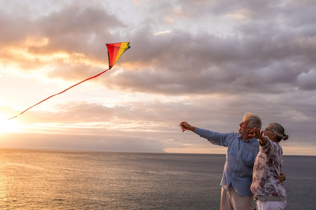 일몰을 배경으로 바다를 배경으로 해변에서 연을 가지고 놀고 즐기는 두 노년층의 초상화 - 활동적인 노인들이 즐겁게 노는 모습