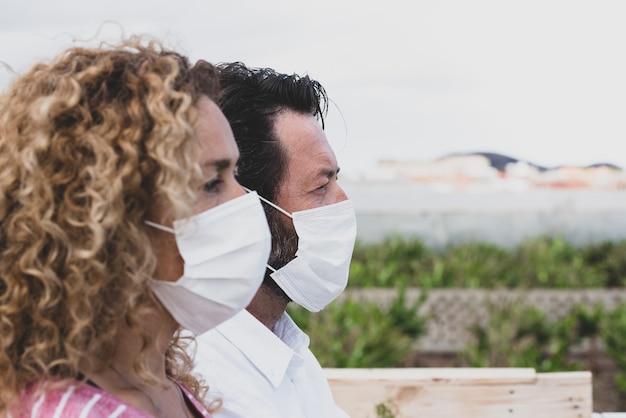 医療用および外科用マスクを着用して目をそらしている2人のクローズアップと肖像画は、covid-19またはあらゆるタイプの新しいウイルス(顔にマスクを付けた女性と隣に男性)を防ぎます。