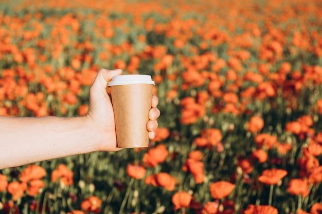 양귀비 밭에 손에 든 갈색 커피 컵을 닫고 부드러운 초점을 맞춥니다. 삶을 느끼는 긍정적인 감정, 마음의 평화. 퇴근 후 자연에서 휴식과 휴식의 개념. 공간을 복사하고 조롱하십시오.
