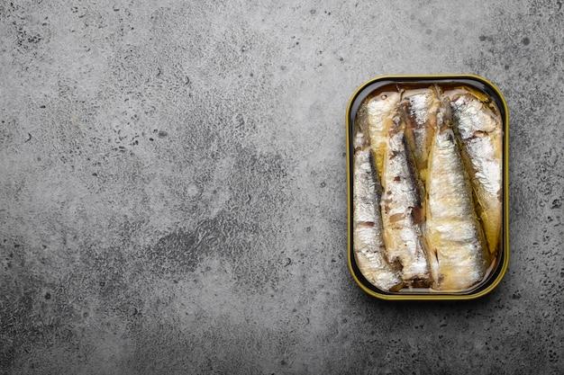 회색 콘크리트 배경 위에 통조림 정어리 통조림을 닫고 위쪽 보기, 텍스트 공간. 편리하고 빠르며 건강에 좋은 음식이자 오메가-3 지방산, 단백질 및 비타민 d의 공급원인 통조림 생선