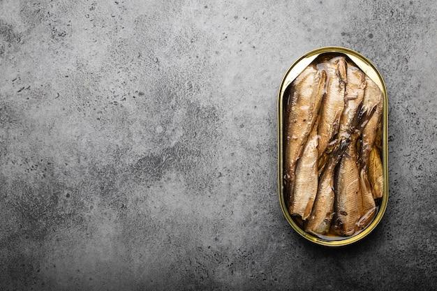 灰色の背景、テキスト用のスペースの上に缶詰のイワシの燻製の上面図をクローズアップします。便利で速くて健康的な食品およびオメガ3脂肪酸、タンパク質、ビタミンdの供給源としての缶詰の魚