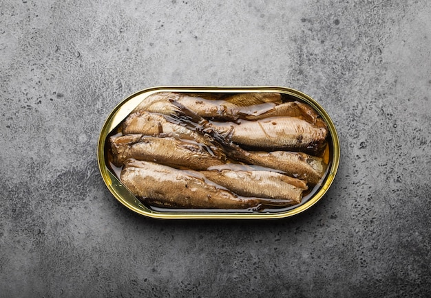 灰色の素朴なコンクリートの背景の上の錫のスモーク缶詰イワシのクローズアップと上面図。便利で速くて健康的な食品およびオメガ3脂肪酸、タンパク質、ビタミンdの供給源としての缶詰の魚