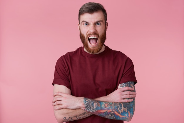 Close up of angry bearded young man with tattooed hand, holding hands crossed, screaming and looking at camera isolated over pink background. people and emotion concept.