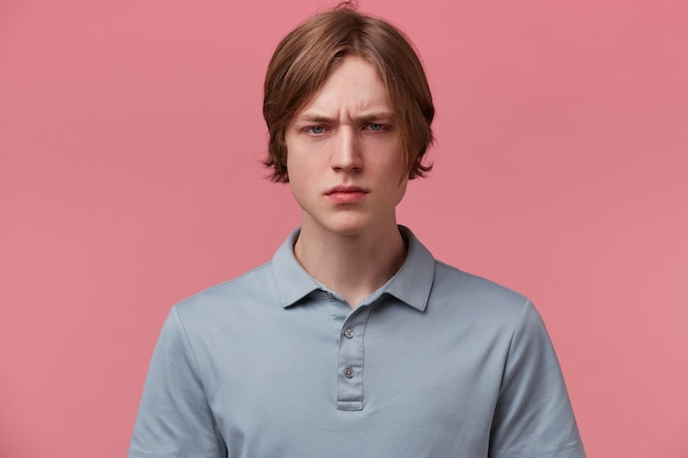 Close up arrabbiato furioso insoddisfatto giovane ragazzo ben pettinato, sopracciglia aggrottate le sopracciglia, occhi aggressivi, vestito con t-shirt polo casual, isolato su sfondo rosa