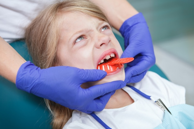 Close up of an angry little girl in dental chair having teeth impressions made by her dentist