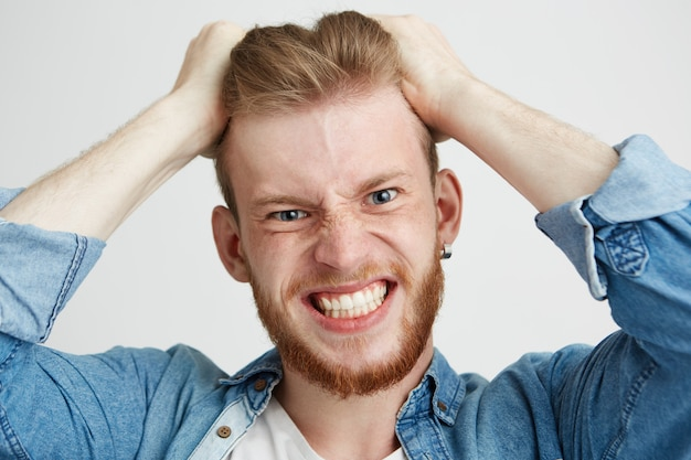 Close up of angry rage young man touching his hair clenched teeth over wite background.