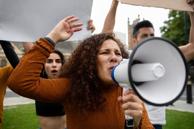 メガホンに向かって叫んでいる怒っている女性をクローズアップ