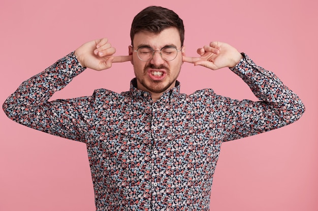 Close up of angry young bearded man dressed in colorful shirt, keeps closed eyes, two fingers close his ears, showing gesture of deafness, ignores someone, over pink wall