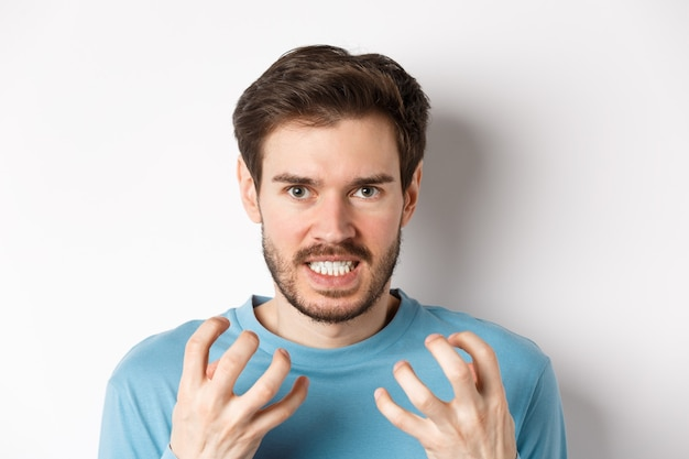 Close up of angry young man with beard, shaking hands mad, squeeze teeth and frowning furious, standing outraged over white background.