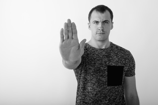 Close up of angry young muscular man showing stop hand sign