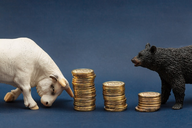 Close-up of animal toys of a bull and a bear standing near coins stacked in columns