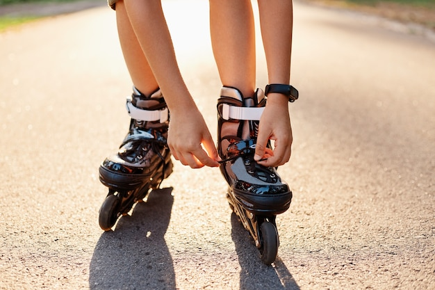 Close-up of an anonymous kid's hands fixing laces on roller blades before skating, unknown child on road in sunny summer day, rollerblading, active lifestyle.