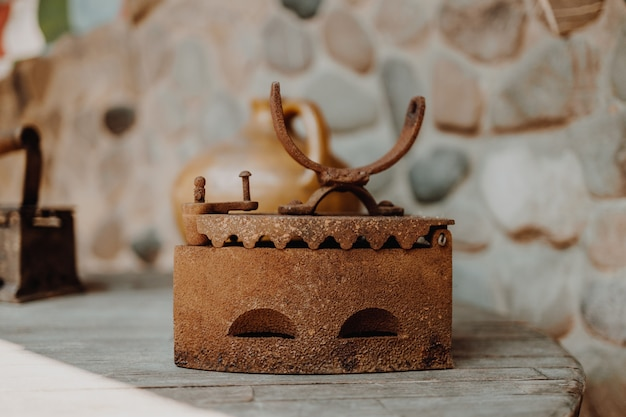 Close up of an antique and rusty iron on wood table background houseworks