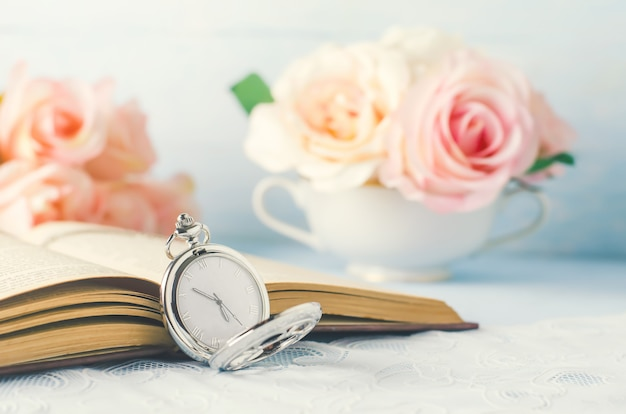 Close up of antique silver pocket watch and opened book with rose flowers on white and blue