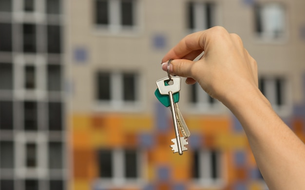Close-up of apartment keys, new house in the background