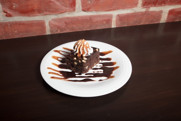 Close up of appetizing chocolate brownie with dark chocolate dressing and vanilla ice crea