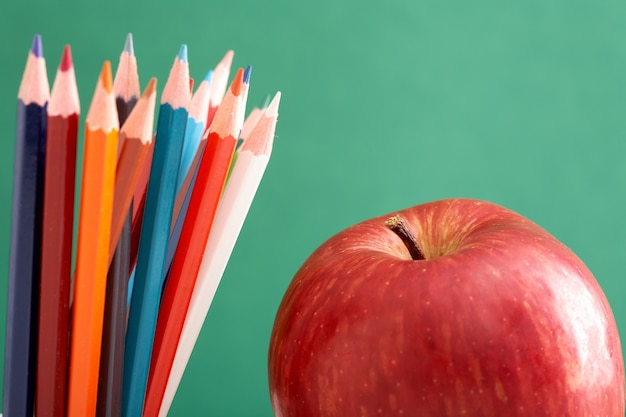 Close-up of an apple and pencils with blackboard background