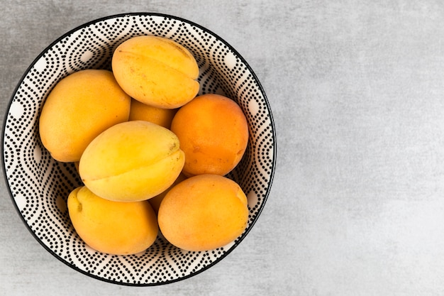 Close up of apricots in bowl on wooden background