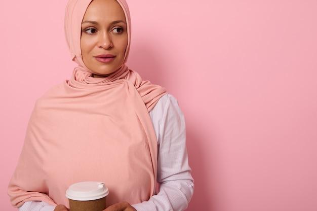확대. 분홍색 히잡과 흰색 셔츠를 입은 아랍 이슬람 아름다운 여성이 재활용 가능한 생태 종이 머그잔을 손에 들고 복사 공간이 있는 컬러 배경 위에 포즈를 취하고 있는 측면을 바라보고 있습니다.
