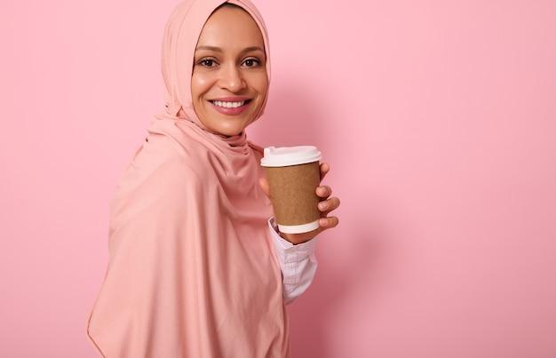 확대. 히잡으로 머리를 덮은 아랍 이슬람 여성은 일회용 판지 테이크아웃 컵을 들고, 이빨 미소를 짓고, 카메라를 보며, 색색의 배경에 4분의 3을 서서, 공간을 복사합니다.