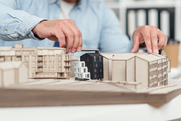 Close up architect's hands at constructing model of buildings and examines his work. urban architecture and design concept.