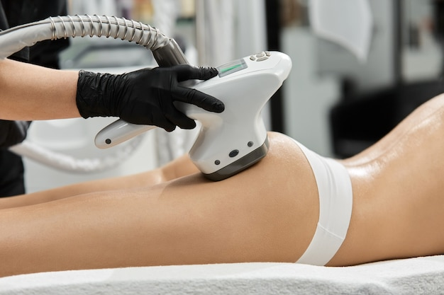 Close-up of arm in black gloves holding cosmetology apparatus on woman buttocks at spa