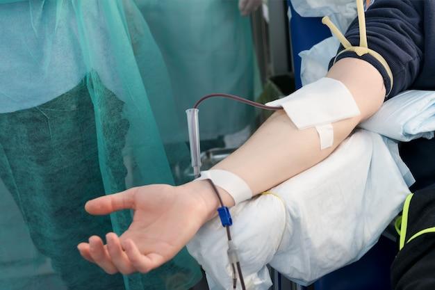 献血をする男性の腕を閉じます。男性のドナーが移動式献血センターで血液を提供します。セレクティブフォーカスを支援する寄付