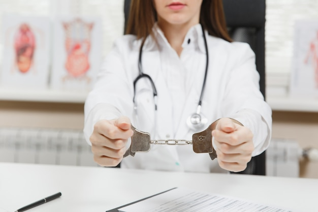 Close up arrested female doctor sitting at desk with medical documents in light office in hospital