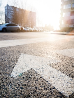 Close-up of arrow on asphalt with view of the street