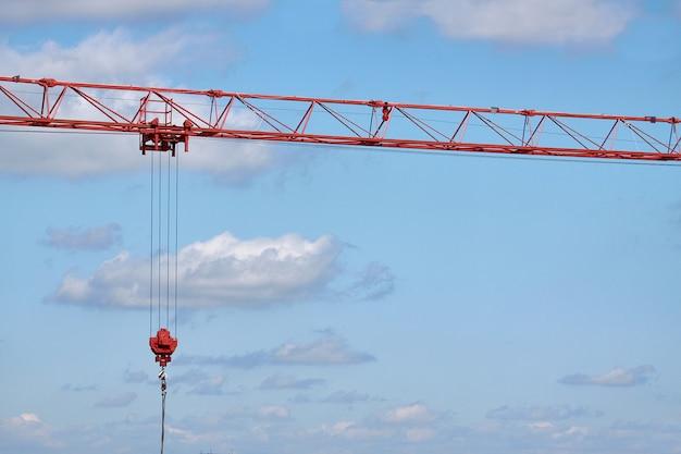 青空、選択と集中の背景に建設用クレーンのクローズアップ矢印