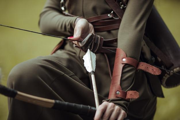 Крупный план. стрелки и лук в женских руках. стрельба из лука мужчина в средневековом костюме.