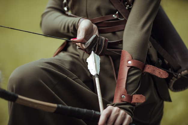 Close-up. arrows and bow in female hands. archery man in medieval costume.