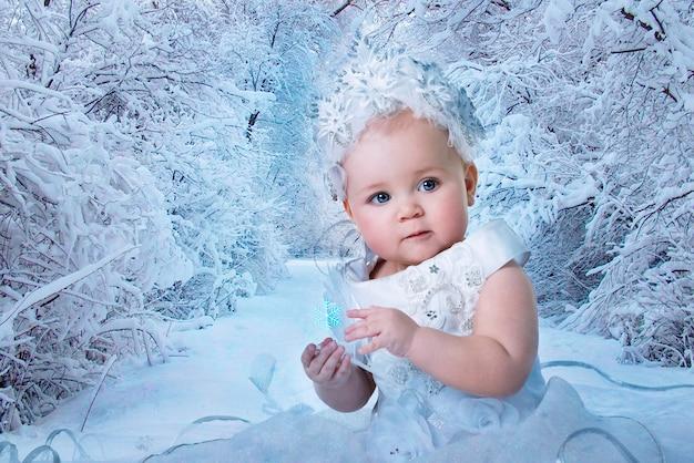 서리가 내린 겨울 배경에서 겨울을 의인화하는 하얀 드레스를 입은 매력적인 파란 눈 소녀의 클로즈업 예술 초상화. 새해 휴일 개념과 크리스마스에 대한 아이들의 사랑