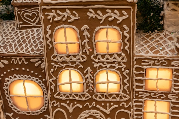Close up of artificial ginger bread house wit lights on christmas and new year holidays interior dec...