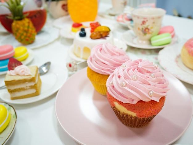 さまざまなデザートやケーキと一緒にピンクの皿に人工のピンクのカップケーキや偽のカップケーキをクローズアップ