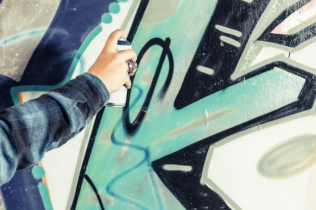 Close-up of an artist's hand painting graffiti on wall