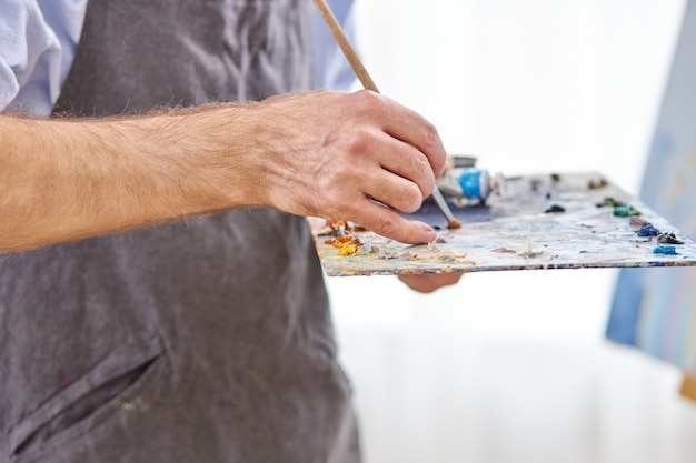 Close-up artist's hands with palette and brush mixing colours, drawing