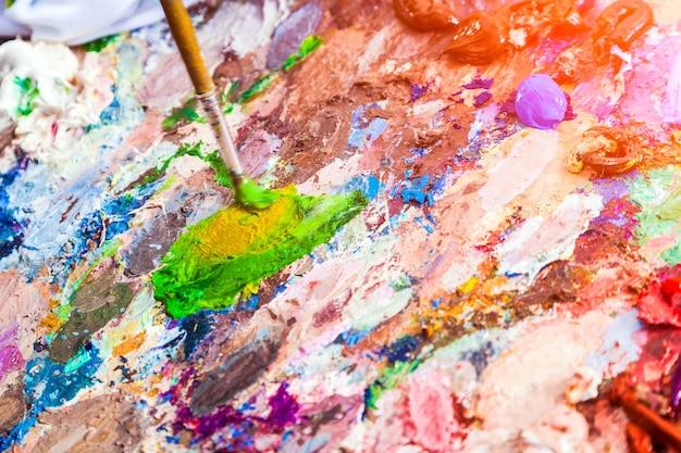 クローズアップアーティストが勝ち、パレットに油絵の具でペイントします