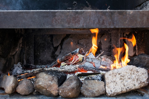 Close-up of the ashes and flames of a barbecue.