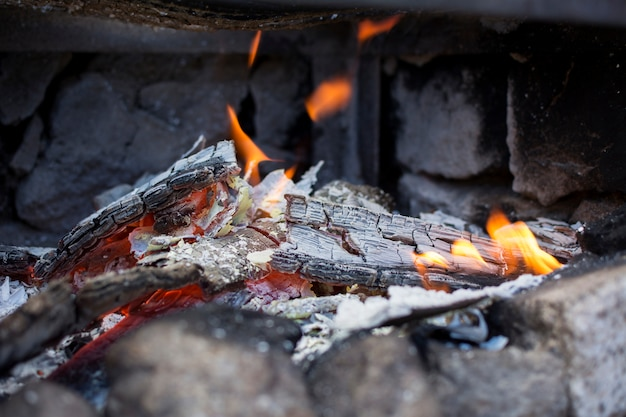 Close-up of the ashes and flames of a grill.