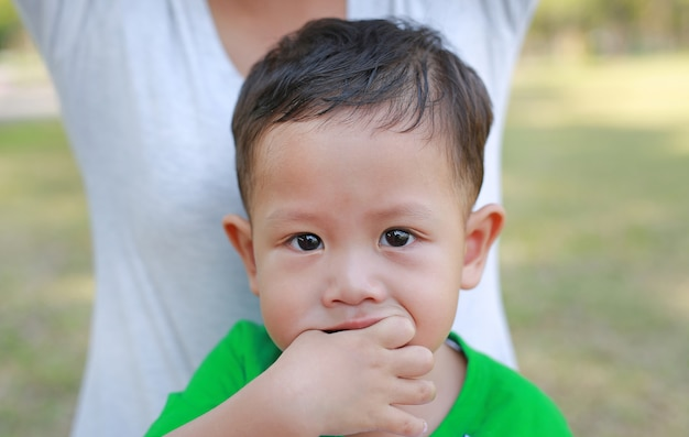 Close up asian baby boy sucking finger in mouth.