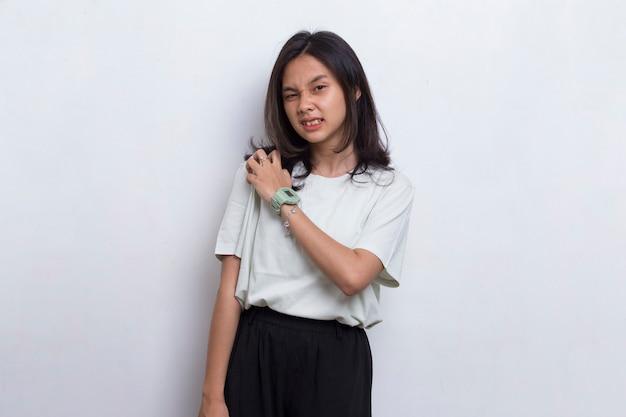 Крупным планом азиатская красивая молодая женщина с болью в травмированном локте на белом фоне