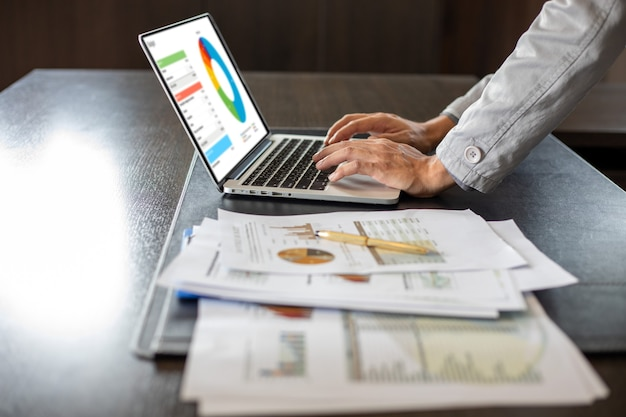 Close up asian businessman using laptop computer  analysis documents and graph financial diagram on office table working