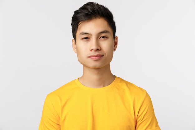 Close-up  asian charming, modern hipster man in yellow t-shirt, smiling with confident, assertive expression, newbie starting work in new company looking forward to meet coworkers