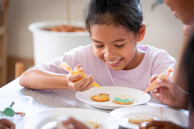 Закройте вверх по азиатской девочке, сжимающей глазурь, чтобы украсить печенье с другом с удовольствием. самодельное искусство для детей и концепция ремесла.