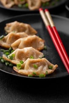 Primo piano del piatto asiatico sulla zolla con le bacchette