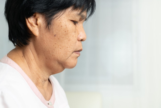 Close-up of asian elder woman face with wrinkled skin condition. side view