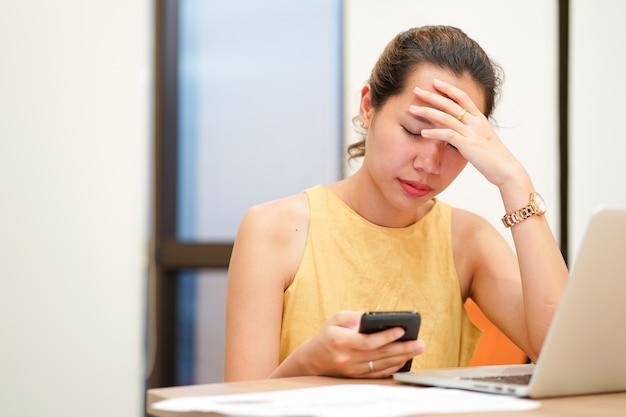 アジアの従業員の女性がオフィスで勤勉でストレスを感じる